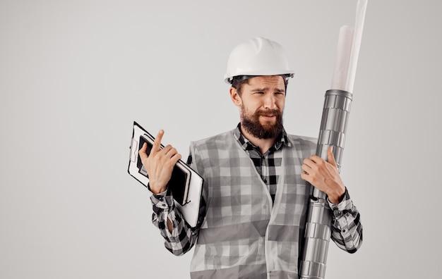 Construtor profissional em um capacete com um tubo nas mãos e documentos