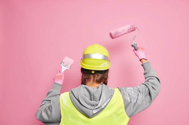 Construtor profissional sem rosto ocupado fazendo a reconstrução de um prédio recuando usa equipamento para pintar paredes, usa capacete de proteção e poses uniformes contra a parede rosa