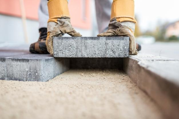 Construtor que coloca lajes de pavimentação exteriores