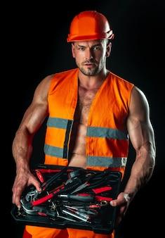 Construtor sexy masculino no capacete de segurança. retrato de homem musculoso em pé sobre fundo preto. arquitetura e construção industrial.