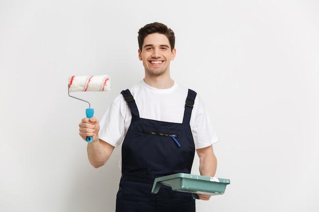 Construtor sorridente mostrando rolo de tinta sobre parede cinza
