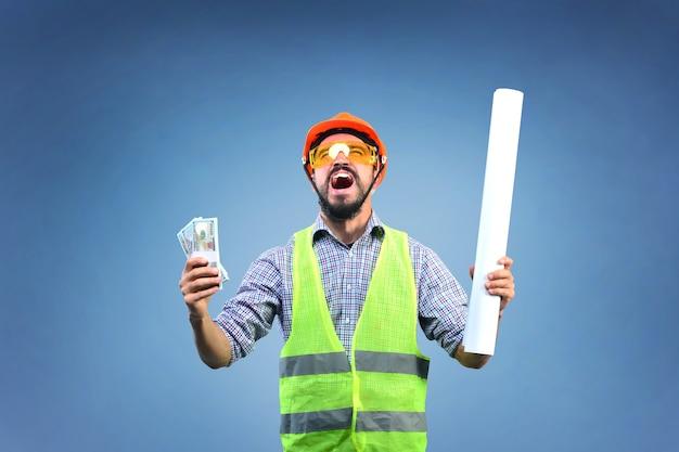 Construtor trabalhador gritando feliz segurando dinheiro na mão direita e projeto concluído na mão esquerda