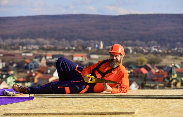 Construtor usa serra. telhado de reparo mestre profissional. instalação em telhado plano. trabalhador de telhados com roupa de trabalho de proteção especial. novo telhado em construção de edifício residencial.