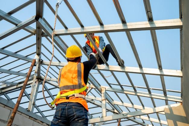 Construtor working on roof of new house, conceito de edifício residencial em construção.