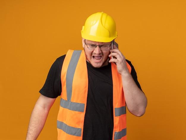 Construtor zangado com colete de construção e capacete de segurança gritando com uma expressão agressiva enquanto fala ao telefone celular em pé sobre um fundo laranja