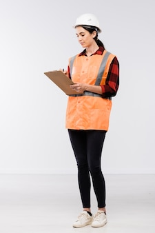 Construtora bonita com capacete de segurança, flanela, perneiras e colete de trabalho fazendo anotações em um documento na frente da câmera, isolada