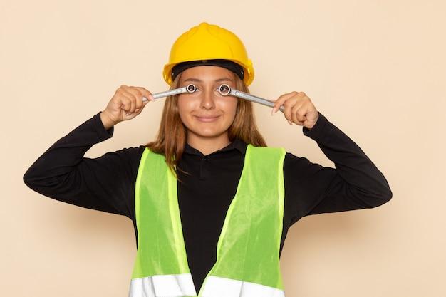 Construtora de frente com capacete amarelo segurando instrumentos de prata com sorriso na parede branca arquiteta