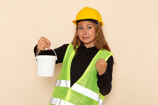 Construtora de frente com capacete amarelo segurando tinta na parede branca construtora arquiteta de construção