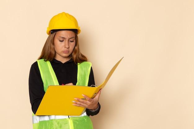 Construtora de frente com capacete amarelo segurando um arquivo amarelo escrevendo notas na parede branca