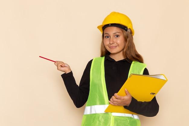 Construtora de frente com capacete amarelo segurando uma lima amarela e lápis na parede branca