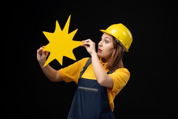 Construtora de frente, de uniforme, segurando uma figura amarela na parede preta