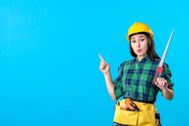 Construtora de frente segurando uma serra azul