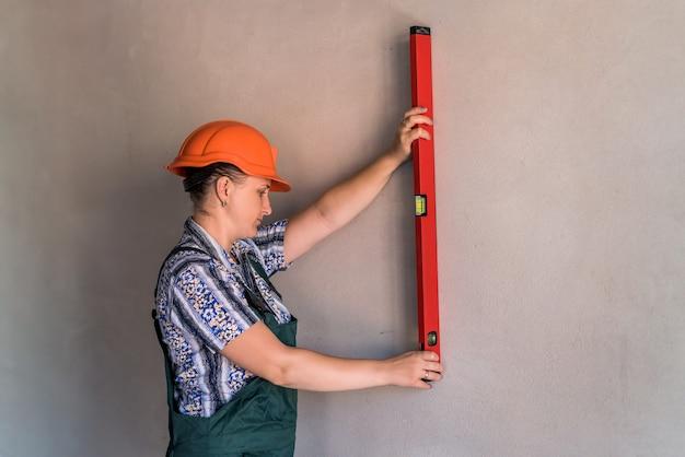 Construtora de mulher medindo parede com nível de água