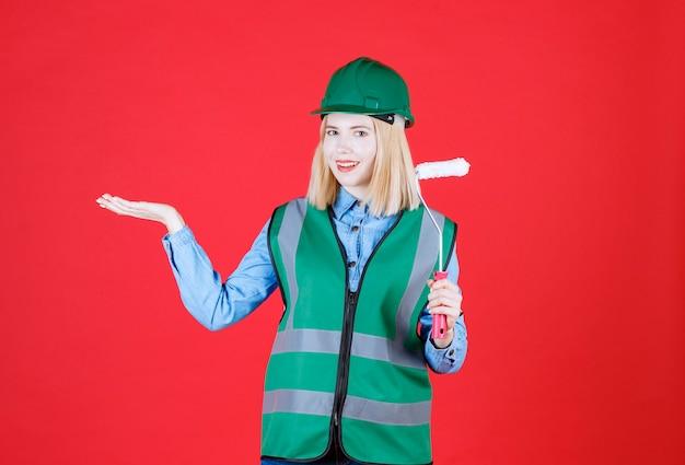 Construtora de uniforme, capacete segurando rolo de pintura e levantando a mão com a palma aberta de lado mostrando algo