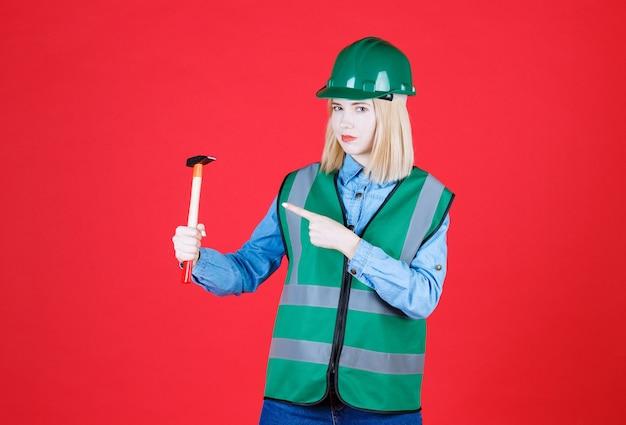 Construtora de uniforme, capacete segurando um martelo enquanto aponta o martelo na parede vermelha