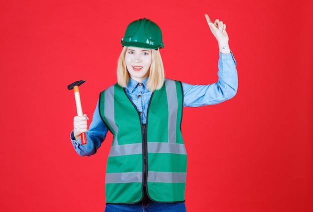 Construtora de uniforme, capacete segurando um martelo enquanto aponta um anúncio na parede vermelha