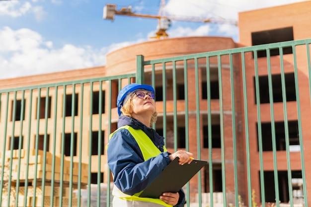 Construtora em um canteiro de obras inspeciona um prédio