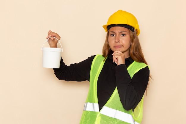 Construtora feminina com capacete amarelo, camisa preta, segurando tinta e pensando na mesa branca, construtora arquiteta