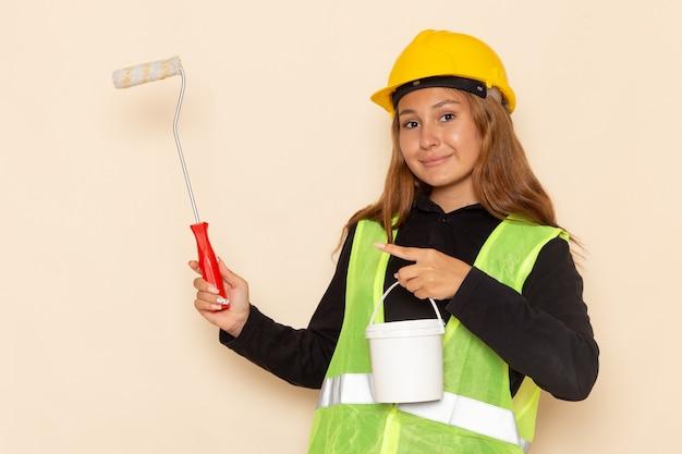 Construtora feminina com capacete amarelo, camisa preta segurando tinta e pincel na mesa branca arquiteta construtora