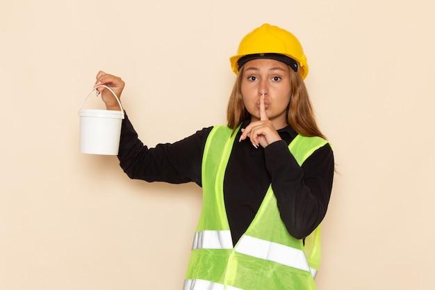 Construtora feminina com capacete amarelo, camisa preta segurando tinta, mostrando o sinal de silêncio na mesa branca arquiteta construtora
