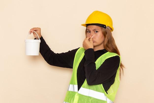 Construtora feminina com capacete amarelo e camisa preta segurando tinta fechando o nariz na mesa branca arquiteta construtora