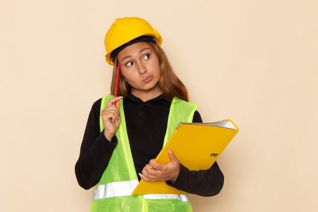 Construtora feminina de vista frontal com capacete amarelo segurando um arquivo amarelo e lápis pensando na mesa branca