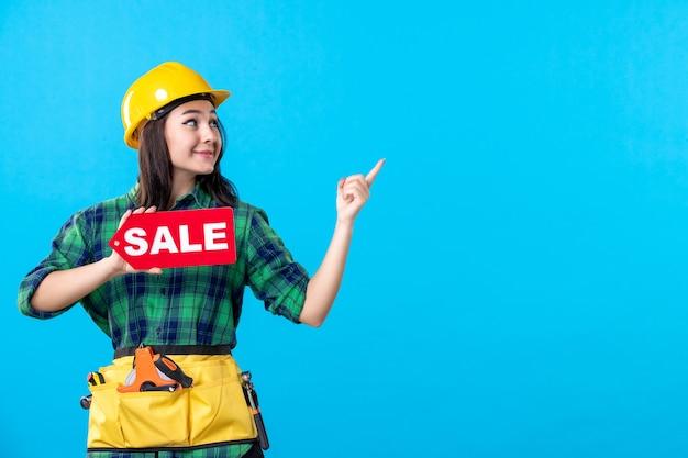 Construtora feminina de vista frontal segurando a escrita vermelha de venda em azul