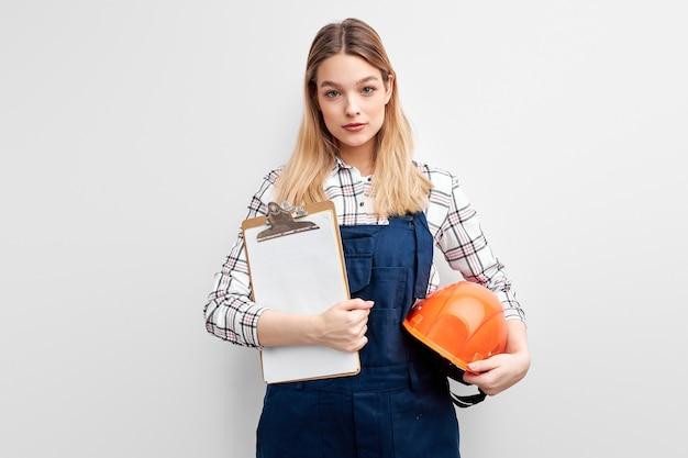 Construtora feminina segurando um capacete laranja e uma prancheta de papel nas mãos e posando