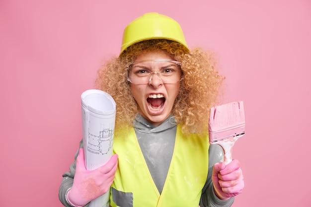 Construtora furiosa e indignada de uniforme segura pincel de pintura e rolo de papel faz conserto de apartamento exclama em voz alta: trabalha em projeto de engenharia isolado sobre parede rosa