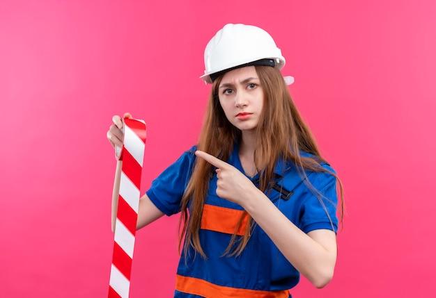 Construtora jovem com uniforme de construção e capacete de segurança segurando fita adesiva apontando com o dedo indicador para ela com rosto sério em pé sobre a parede rosa