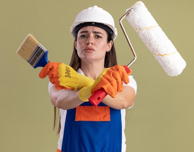 Construtora jovem rígida de uniforme e luvas segurando e cruzando pincel com escova de rolo isolada na parede verde oliva