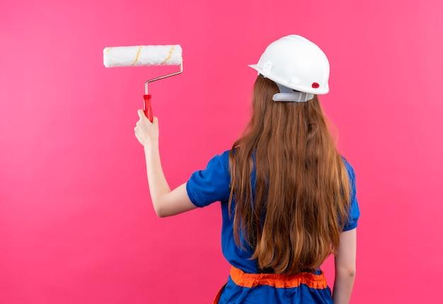 Construtora jovem trabalhadora com uniforme de construção e capacete de segurança em pé, de costas para pintar com rolo de pintura sobre a parede rosa