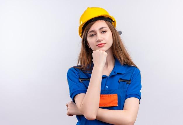 Construtora jovem trabalhadora em uniforme de construção e capacete de segurança em pé com a mão no queixo com expressão pensativa pensando sobre a parede branca