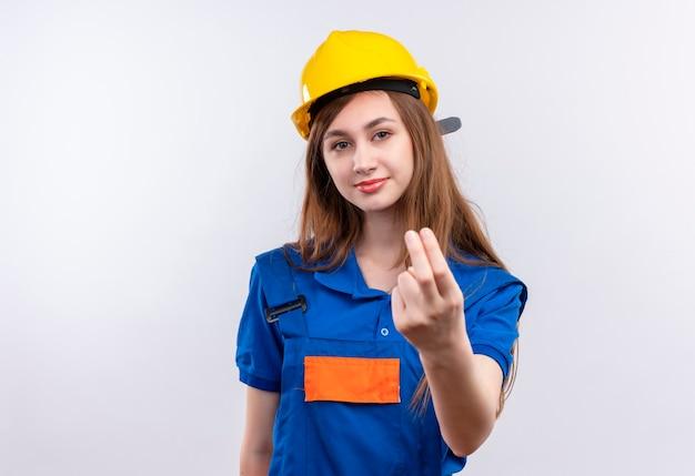 Construtora jovem trabalhadora em uniforme de construção e capacete de segurança, fazendo um gesto com a mão, parecendo confiante em pé sobre a parede branca