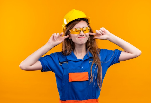 Construtora jovem trabalhadora em uniforme de construção e capacete de segurança fechando as orelhas com os dedos para o barulho do som alto em pé sobre a parede laranja