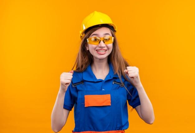 Construtora jovem trabalhadora em uniforme de construção e capacete de segurança, punhos levantados e feliz, regozijando-se com seu sucesso em pé sobre a parede laranja