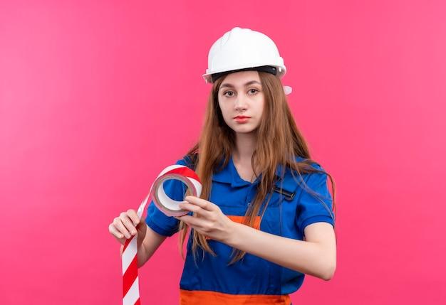 Construtora jovem trabalhadora em uniforme de construção e capacete de segurança segurando fita adesiva e olhando com cara séria em pé sobre a parede rosa