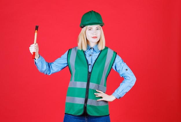 Construtora séria com capacete verde e uniforme, mantendo o martelo isolado no vermelho