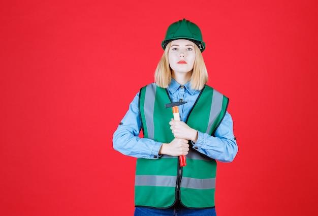Construtora séria com capacete verde e uniforme segurando o martelo com as duas mãos