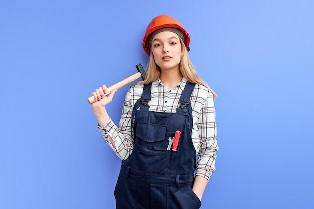 Construtora séria segurando um martelo, vestida de macacão e olhando para a câmera, pronta para consertar coisas quebradas