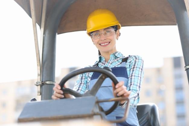 Construtora sorridente com capacete dirigindo equipamento de construção