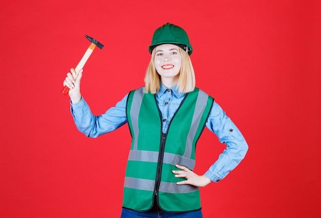 Construtora sorridente em uniforme verde e capacete mantendo o martelo enquanto sorri isolado