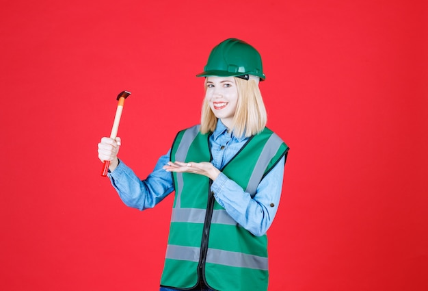 Construtora usando capacete verde e uniforme, segurando um martelo e abrindo a mão como uma palma na parede vermelha