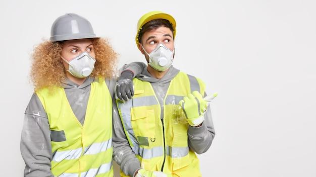 Construtores de capacetes de segurança, respiradores e roupas de trabalho ficam próximos um do outro.
