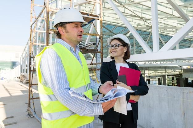Construtores de construção, homem e mulher no canteiro de obras, equipe de industriais.
