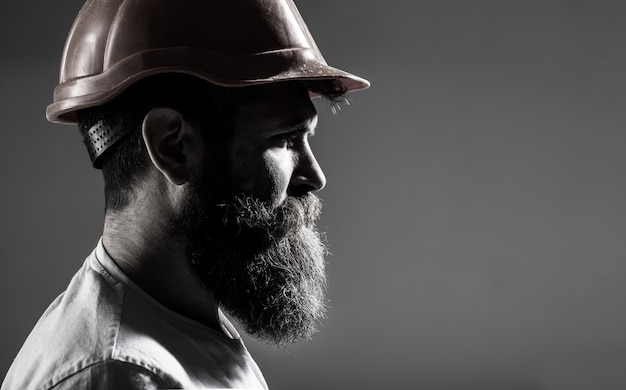 Construtores de homem, indústria. trabalhador de homem barbudo com barba na construção de capacete ou capacete. construtor de retratos, engenheiro civil trabalhando. construtor em capacete, capataz ou reparador em capacete