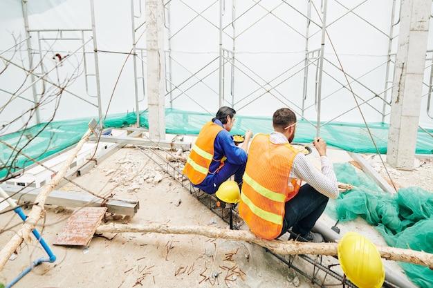 Construtores em vists laranja sentados na sala de um prédio em construção e saboreando um delicioso ramen no almoço, vista de trás