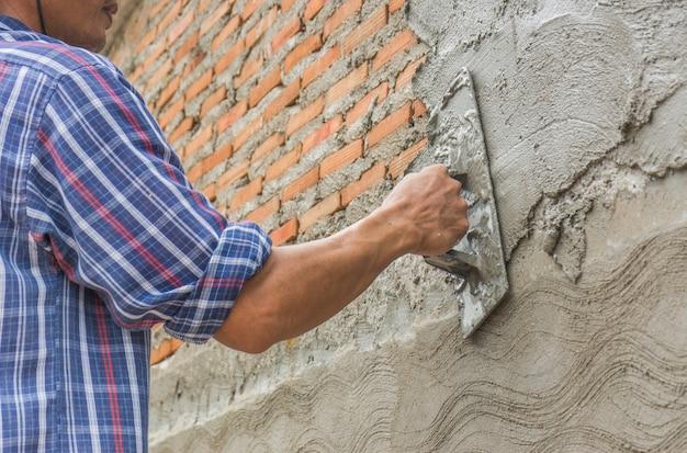 Construtores estão rebocando as paredes da casa com asseio.