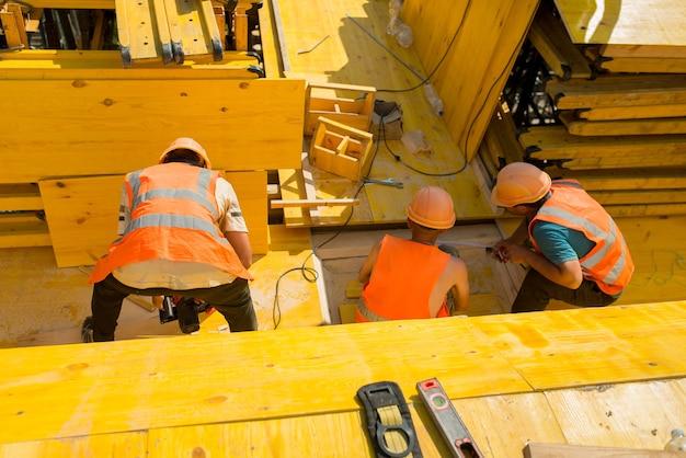 Construtores instalando formas de painéis de madeira em um canteiro de obras