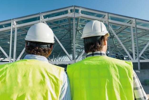 Construtores masculinos no telhado do canteiro de obras, vista traseira